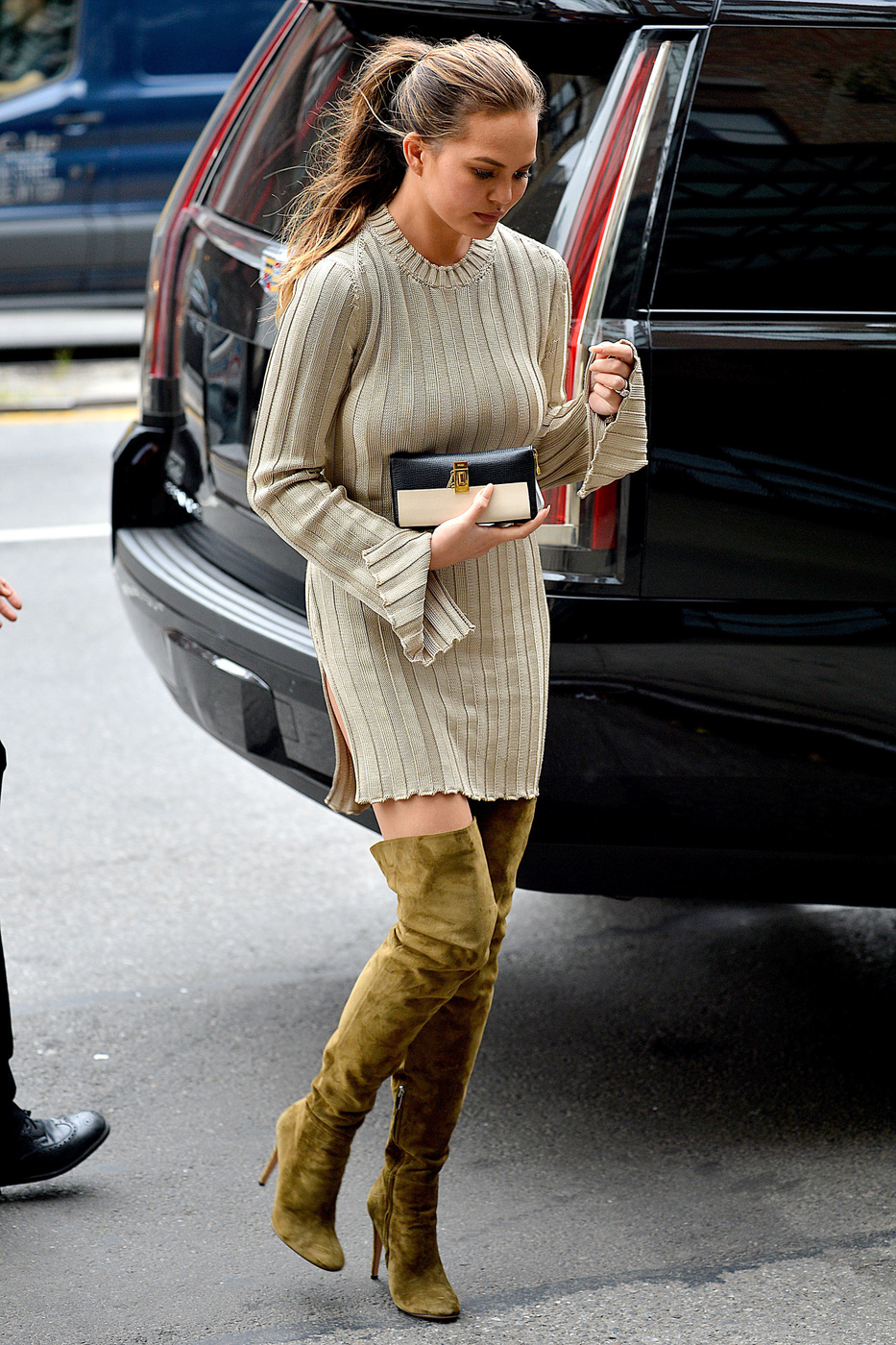 Chrissy Teigen rocks a pair of over the knee suede boots and wool sweater dress as she arrives at her hotel